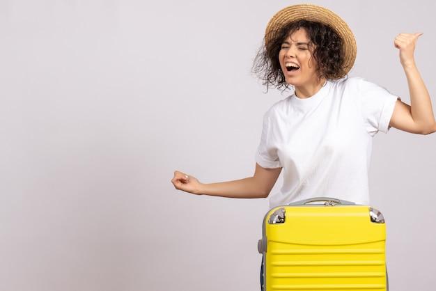 Vorderansicht junge frau mit gelber tasche, die sich auf die reise vorbereitet und auf weißem hintergrund urlaub reise farbe flug touristische flugzeug rest freut