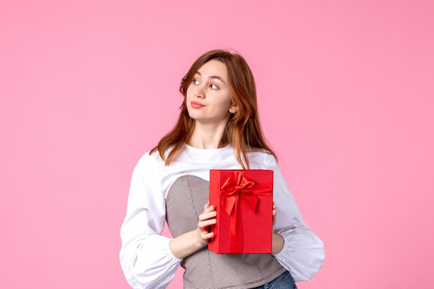 Vorderansicht junge frau mit geschenk im roten paket auf rosa hintergrund liebesdatum märz horizontales geschenk parfüm frau foto geld gleichheit