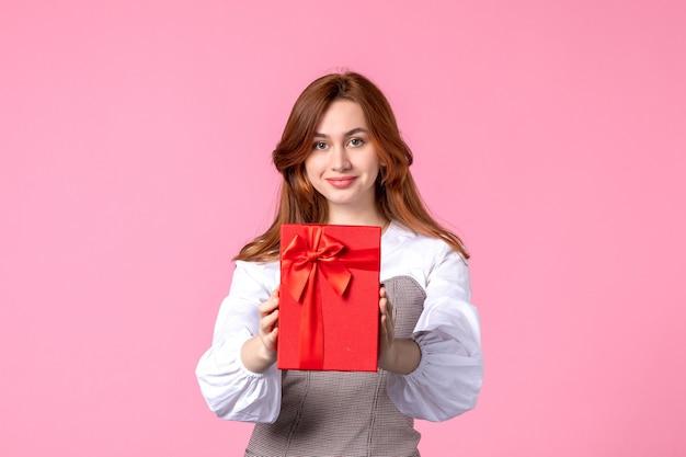 Vorderansicht junge frau mit geschenk im roten paket auf rosa hintergrund liebesdatum märz horizontales geschenk parfüm gleichheit frau fotogeld