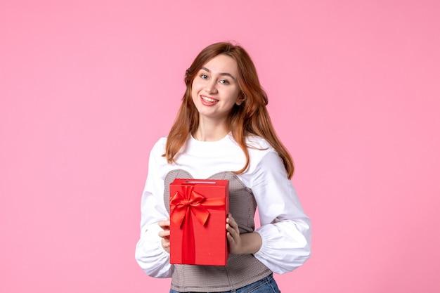 Vorderansicht junge frau mit geschenk in rotem paket auf rosa hintergrund marschieren horizontale sinnliche geschenk foto geld gleichheit frau