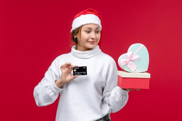 Vorderansicht junge frau mit geschenken und bankkarte auf dem roten hintergrund