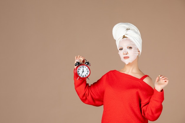 Vorderansicht junge frau mit gesichtsmaske, die uhr auf rosa hintergrund hält