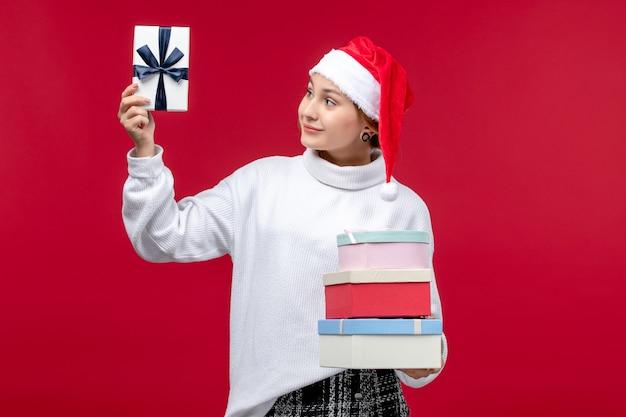 Vorderansicht junge frau mit neujahrsgeschenken auf hellrotem hintergrund