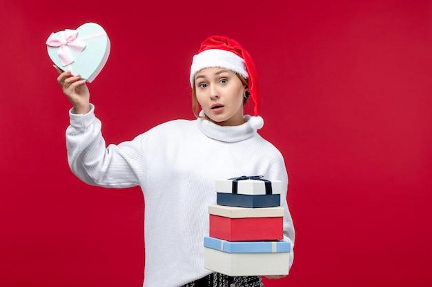 Vorderansicht junge frau mit neujahrsgeschenken auf rotem hintergrund