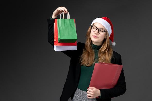 Vorderansicht junge frau mit paketen auf dunklem schreibtischgeschenk neujahrsweihnachten