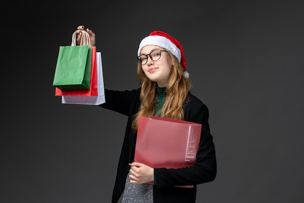 Vorderansicht junge frau mit paketen auf dunklem wandgeschenk neujahrsweihnachtsgeschenk