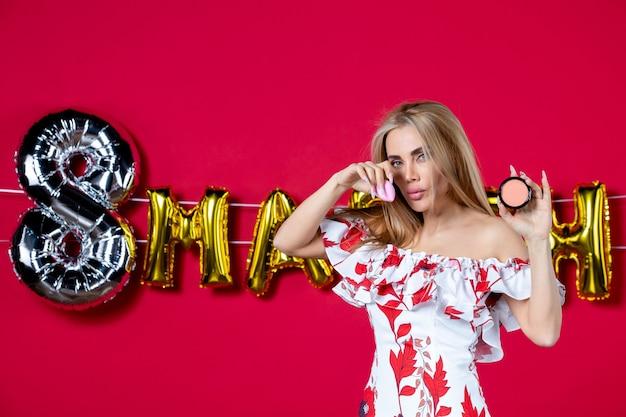 Vorderansicht junge frau mit puderbox auf märz dekoriert roten hintergrund wimpern haut make-up schönheit hautpflege glanz horizontalen glamour