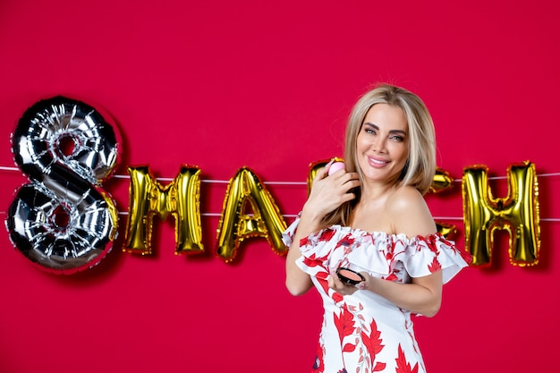 Vorderansicht junge frau mit puderbox auf märz dekoriert roten hintergrund wimpernhaut horizontale make-up glamour schönheit hautpflege
