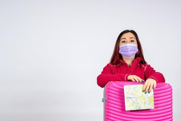 Vorderansicht junge frau mit rosa tasche in der maske, die karte auf weißer wandfarbvirus-urlaubspandemie-reisefrau covid- hält