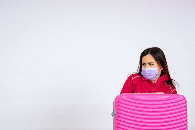 Vorderansicht junge frau mit rosa tasche in maske auf weißer wand pandemievirus frau urlaub covid-farbe reise