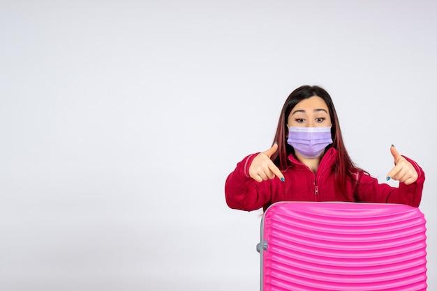 Vorderansicht junge frau mit rosa tasche in maske auf weißer wand virus frau urlaub covid farbe pandemie