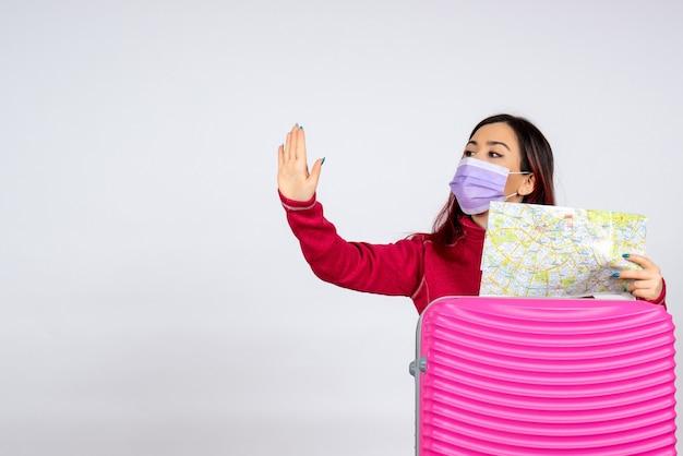 Vorderansicht junge frau mit rosa tasche in maske, die karte auf weißer wandfrau farbvirus-urlaubsreise covid- hält