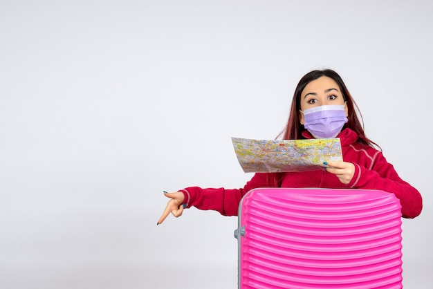 Vorderansicht junge frau mit rosa tasche in maske hält karte auf weißer wand frau farbvirus urlaub pandemie reise covid-