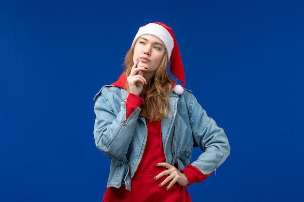 Vorderansicht junge frau mit roter kappe, die auf blauem raum denkt