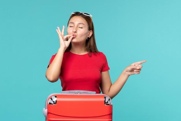 Vorderansicht junge frau mit roter tasche, die für urlaub auf dem blauen raum vorbereitet