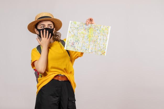 Vorderansicht junge frau mit rucksack hält karte hoch und legt sich die hand auf den mund