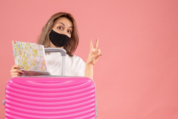 Vorderansicht junge frau mit schwarzer maske, die karte hält und siegeszeichen hinter rosa koffer
