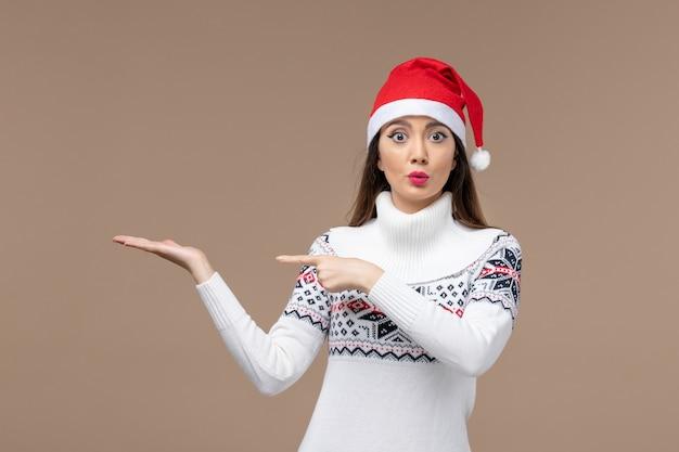Vorderansicht junge frau mit überraschtem ausdruck auf braunem hintergrundfeiertagsemotionsweihnachten