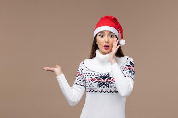 Vorderansicht junge frau mit weihnachtsumhang auf dem braunen hintergrundfeiertagsemotionsweihnachten