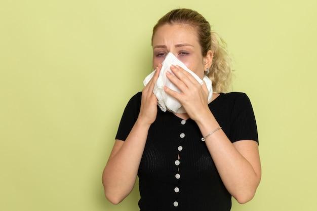 Vorderansicht junge frau mit weißem handtuch um den hals, die sich sehr krank und krank fühlt und ihre nase auf hellgrüner wandkrankheit krank macht. weibliche gesundheit