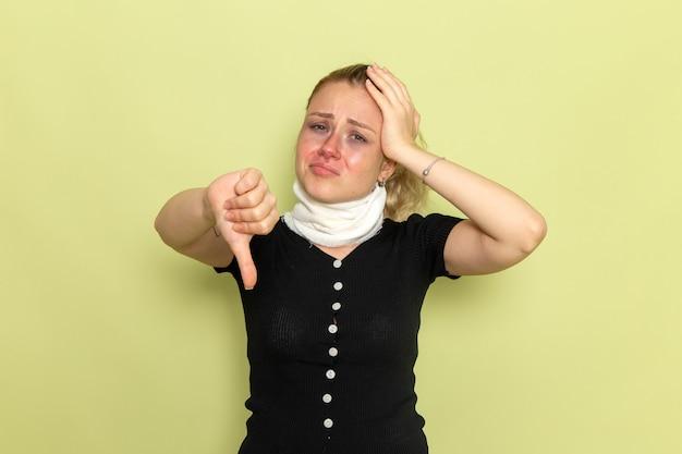 Vorderansicht junge frau mit weißem handtuch um ihren hals, der sich sehr krank und krank fühlt, im gegensatz zu zeichen auf grüner wandkrankheit krankheit weibliche farbgesundheit