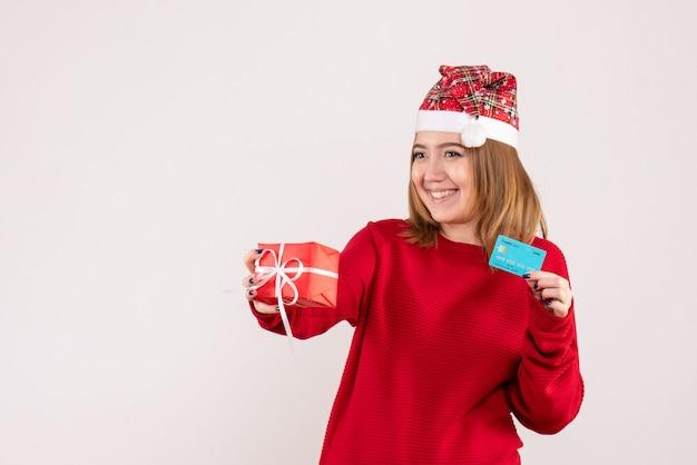 Vorderansicht junge frau mit wenig weihnachtsgeschenk und bankkarte