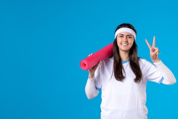 Vorderansicht junge frau mit yogamatte auf blauer wand