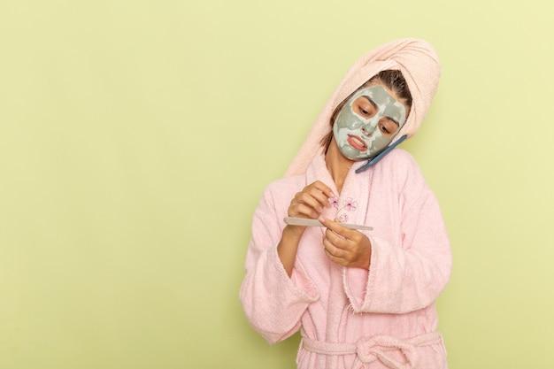 Vorderansicht junge frau nach der dusche im rosa bademantel, der am telefon auf grüner oberfläche spricht