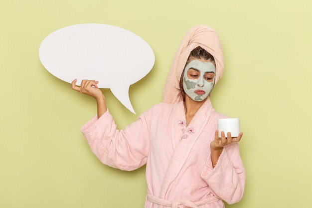 Vorderansicht junge frau nach der dusche im rosa bademantel, der creme und weißes zeichen auf grüner oberfläche hält