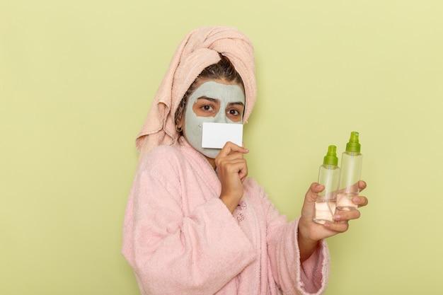 Vorderansicht junge frau nach der dusche im rosa bademantel, der sprays und karte auf hellgrüner oberfläche hält