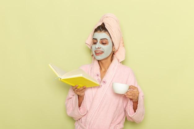 Vorderansicht junge frau nach dusche im rosa bademantel, der kaffee trinkt und heft auf grüner oberfläche liest