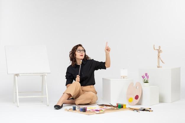 Vorderansicht junge frau sitzt im zimmer mit farben und staffelei auf weißem hintergrund