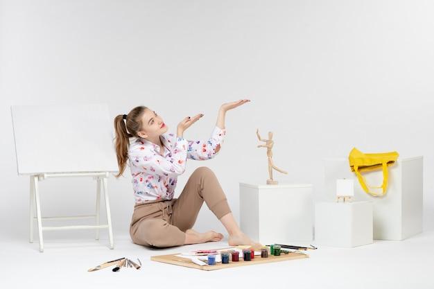 Vorderansicht junge frau sitzt mit farben staffelei und pinsel auf weißem hintergrund