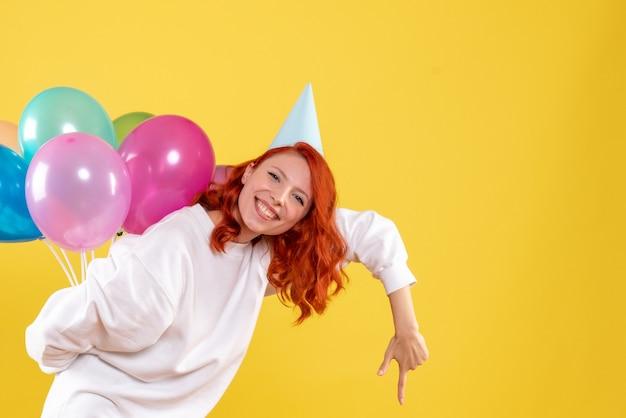 Vorderansicht junge frau versteckt bunte luftballons hinter ihrem rücken neujahrsparty farbe weihnachtsfrau
