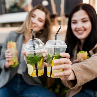 Vorderansicht junge frauen, die einige u-boote und cocktails genießen