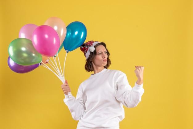 Vorderansicht junge hübsche frau, die luftballons auf gelber farbe weihnachten neujahr emotion frau hält