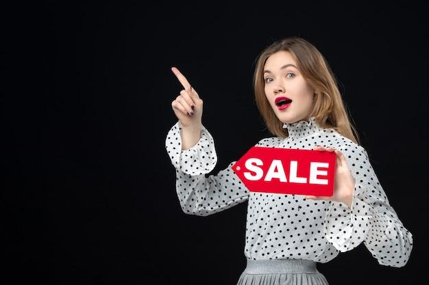 Vorderansicht junge hübsche frau, die verkaufsschreiben auf schwarzer wand hält, farben einkaufen mode foto frau emotion rot