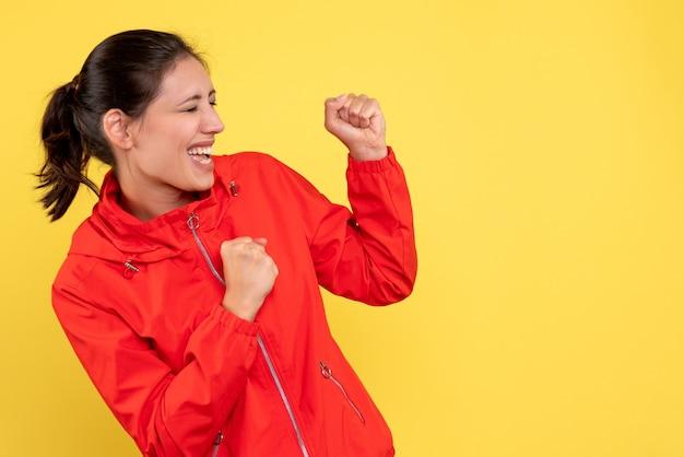 Vorderansicht junge hübsche frau im roten mantel auf gelbem hintergrund