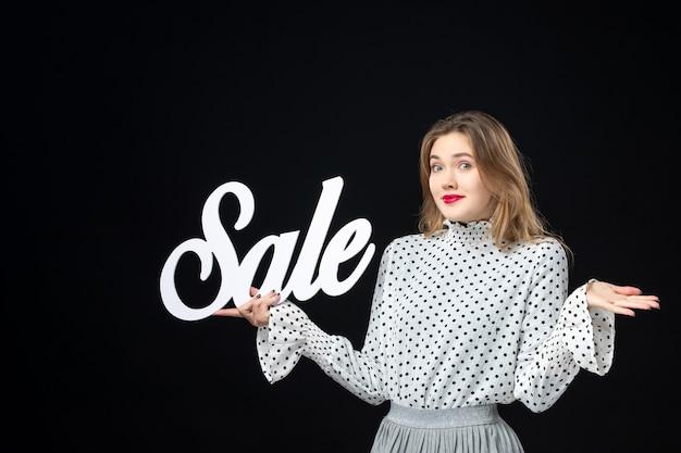 Vorderansicht junge hübsche frau mit verkauf schreiben auf schwarzem wandmodell shopping schönheit mode emotion farben