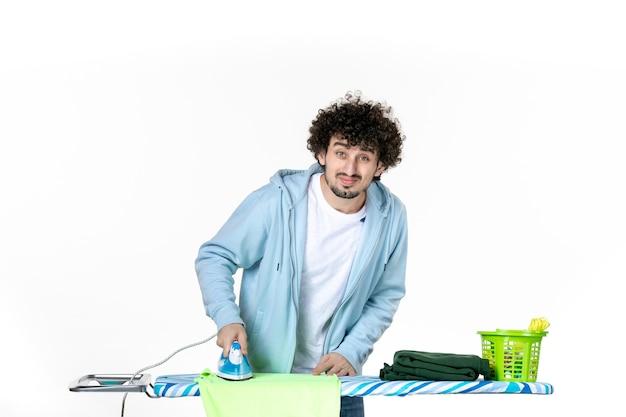 Vorderansicht junge männliche bügeltuch an bord auf weißem hintergrund eisenfarbe mann reinigung hausarbeit wäsche foto kleidung