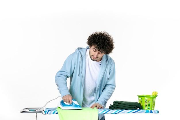 Vorderansicht junge männliche bügeltuch an bord auf weißem hintergrund eisenfarbe mann reinigung wäsche foto kleidung hausarbeit