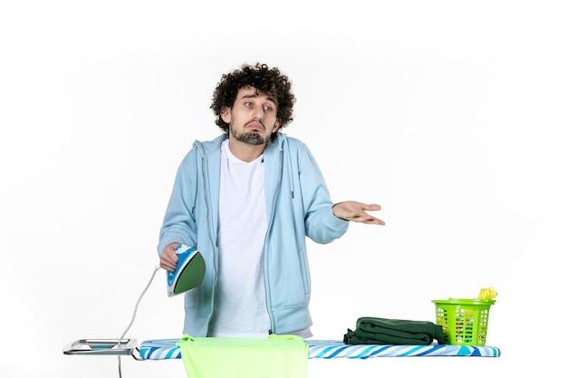 Vorderansicht junge männliche bügeltuch an bord auf weißem hintergrund eisenfarbe mann reinigung wäsche fotos kleidung hausarbeit