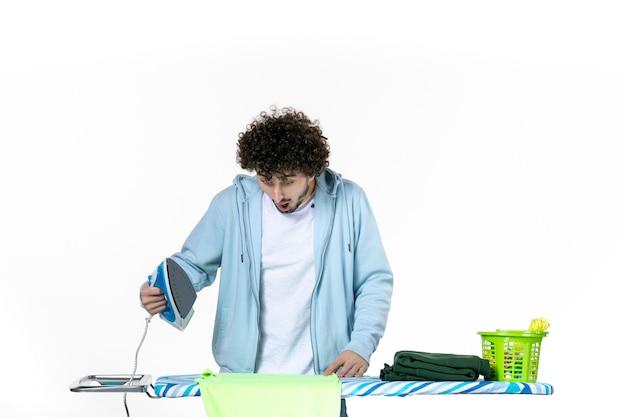 Vorderansicht junge männliche bügeltuch und brennen es auf weißem hintergrund eisenfarbe mann reinigung hausarbeit wäsche foto kleidung