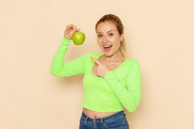 Vorderansicht junge schöne frau im grünen hemd, das grünen frischen apfel auf cremewandfruchtmodell-frau ausgereift hält