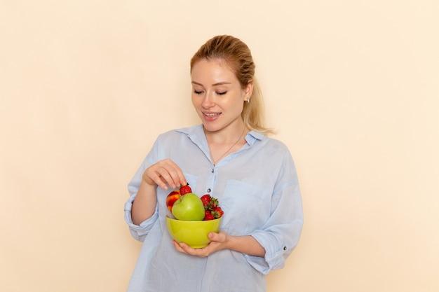 Vorderansicht junge schöne frau im hemd, das platte mit früchten auf den cremefarbenen wandfrucht-reifen modellfrauenhaltung hält