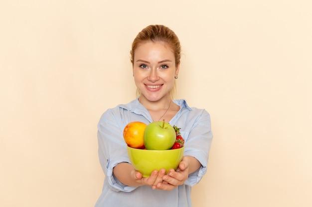 Vorderansicht junge schöne frau im hemd, das platte mit früchten hält und auf cremewandfruchtmodellmodell-frauenpose dame lächelt