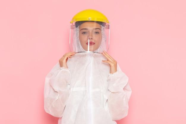 Vorderansicht junge schöne frau im speziellen weißen anzug, der schutzhelm auf der rosa raum-spezialanzug-mädchenfrau trägt