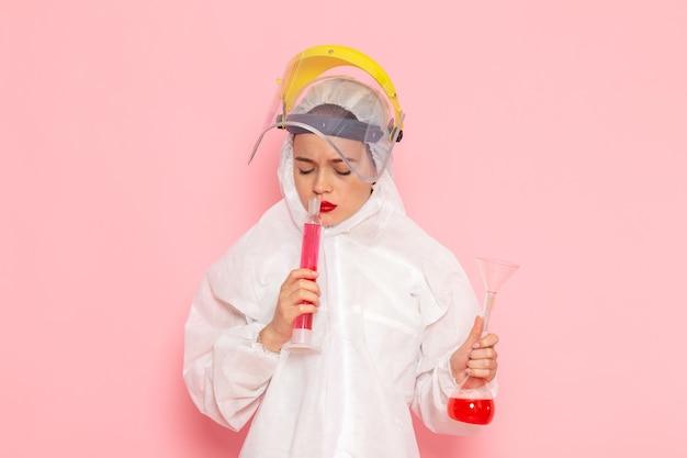 Vorderansicht junge schöne frau im speziellen weißen anzug, die schutzhelmhaltelösung auf der rosa raum-spezialanzugfrau trägt