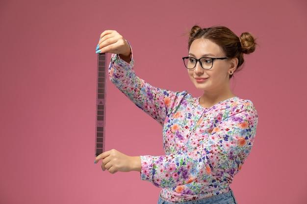 Vorderansicht junge schöne frau in blume entworfenes hemd und blaue jeans, die altes kinoband auf dem rosa hintergrund halten