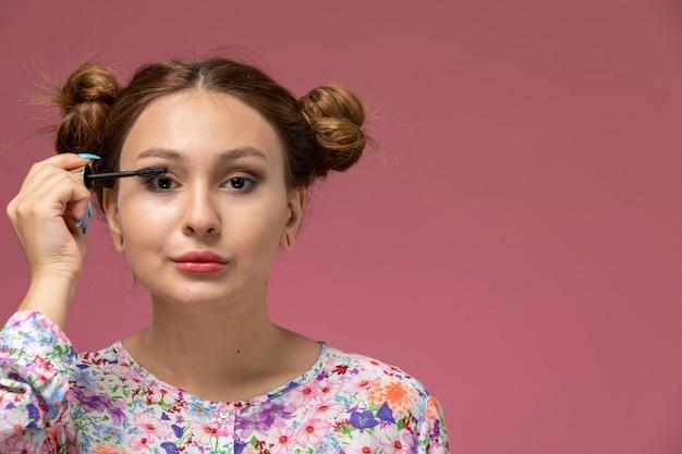 Vorderansicht junge schöne frau in blume entworfenes hemd und blaue jeans, die ein make-up auf dem rosa hintergrund tun